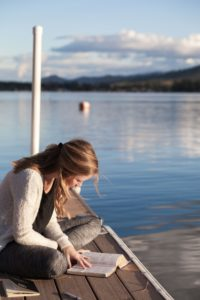 a young woman reading at the lake