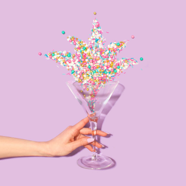 a glass you might use for a cannabis special event, it has a leaf made out of confetti in it
